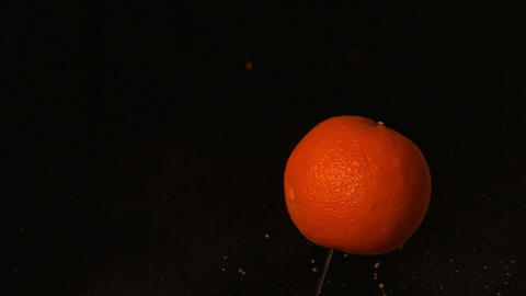 Arrow shooting through orange on black background Footage