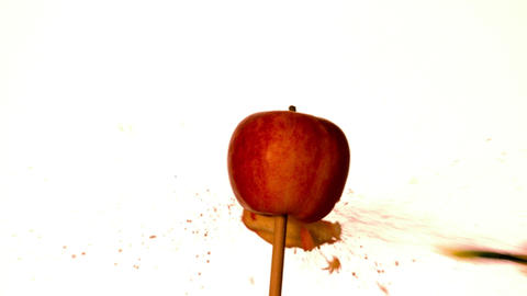 Arrow shooting through red apple on white background Stock Video Footage