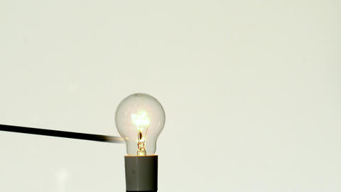 Arrow shooting through light bulb on white background Stock Video Footage