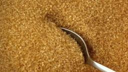 Teaspoon scooping up golden sugar Live Action