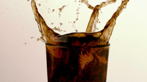 Ice cube falling into glass of soda Stock Video Footage