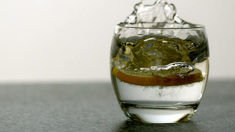 Slice of orange falling into glass of water Stock Video Footage