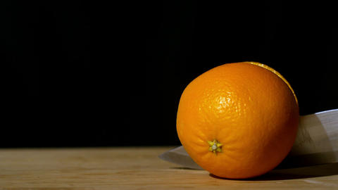 Knife slicing orange in half Footage