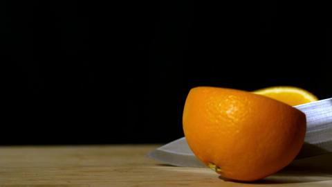 Knife slicing orange in half Stock Video Footage