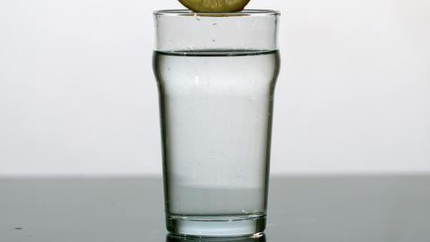 Lemon slice falling into pint of water Stock Video Footage