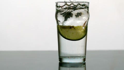 Apple wedge falling into pint of water Footage