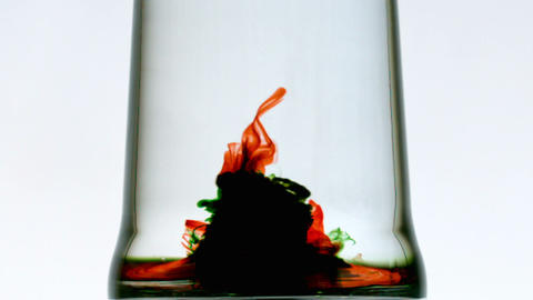 Colourful whirlpool in pint of water on white background Stock Video Footage
