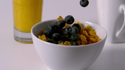 Blueberries pouring into cereal bowl at breakfast table Footage