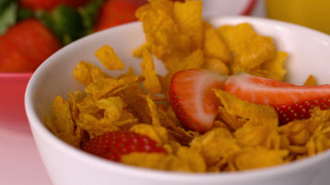 Strawberries pouring into cereal bowl at breakfast table Stock Video Footage