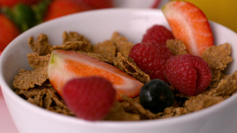 Berries pouring into cereal bowl at breakfast table Stock Video Footage
