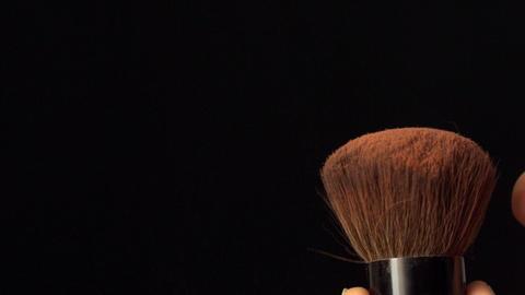Womans finger flicking powder brush Stock Video Footage