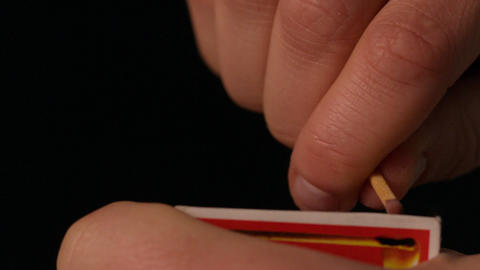 Hand lighting a match on black background Stock Video Footage