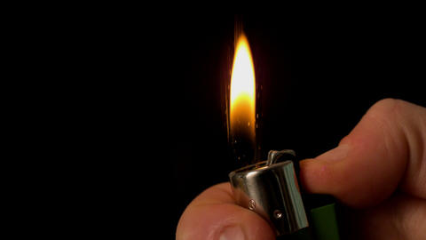 Hand lighting a lighter on black background Footage