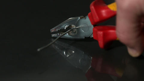 Hand cutting wire with pliers Stock Video Footage