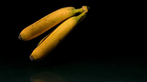 Bananas falling on black background Stock Video Footage