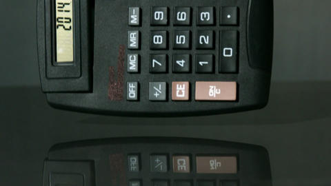 Calculator falling on black background Stock Video Footage