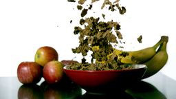 Cereal falling in a bowl beside fruit Stock Video Footage