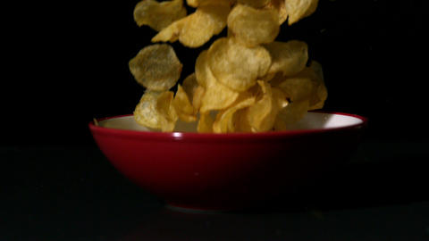Chips falling into bowl on black surface Footage