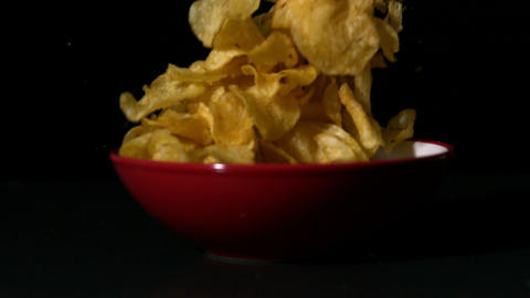 Chips falling into bowl on black surface Stock Video Footage