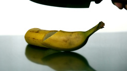 Man slicing banana with large knife Footage