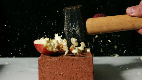 Hammer smashing apple over bricks Footage