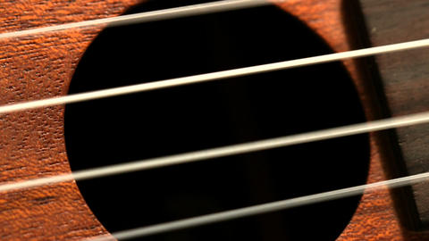 Hand strumming guitar strings close up Live Action