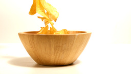 Chips falling in wooden bowl Footage