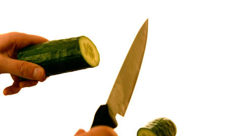 Hand slicing a cucumber on white background Footage