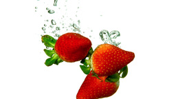 Strawberries falling in water on white background Footage