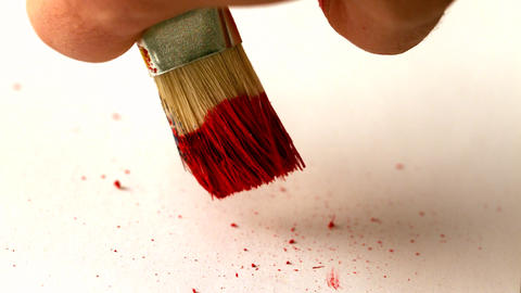 Finger flicking red paint off brush Footage
