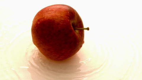 Apple spinning on wet white surface Footage