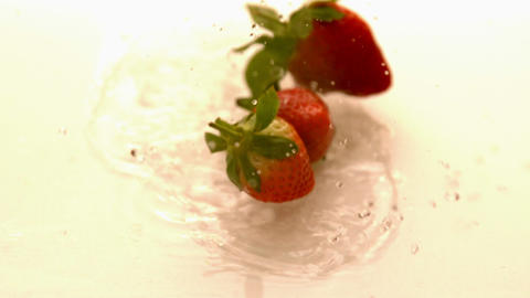 Strawberries falling on white wet surface Footage