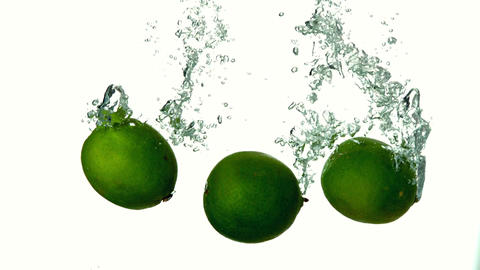 Limes plunging into water on white background Footage