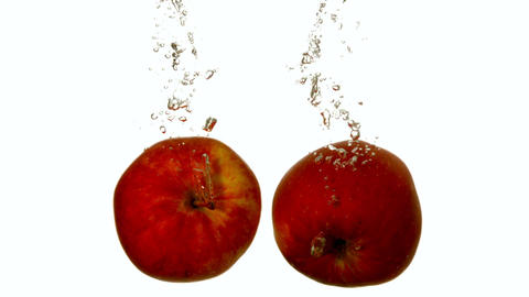 Red apples plunging into water on white background Footage