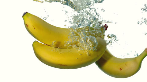 Bananas plunging into water on white background Footage