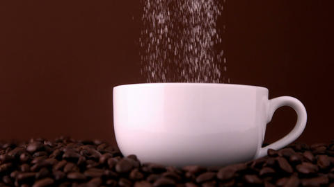 Sugar pouring into white coffee cup Footage