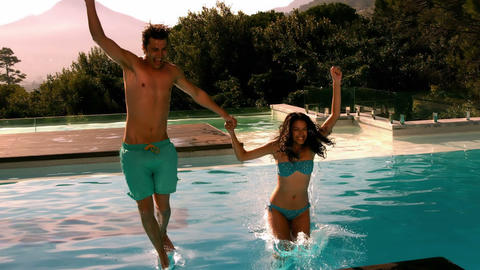 Happy couple jumping in swimming pool together Filmmaterial