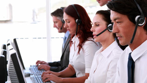 Call centre agents working and talking on headsets Footage