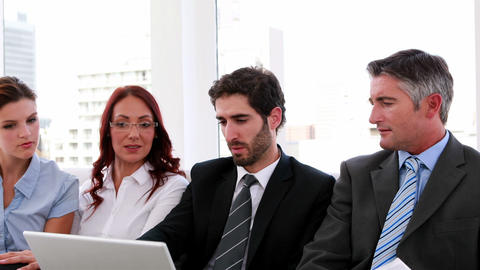 Business team sitting on couch having a meeting using laptop Footage
