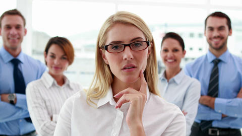 Businesswoman looking at camera with colleagues behind her Footage