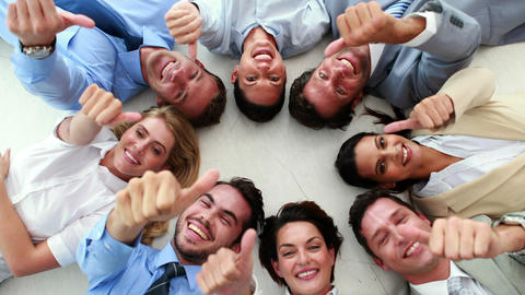 Business people lying in a circle showing thumbs u Footage