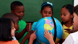 Pupils looking at the globe in classroom Footage
