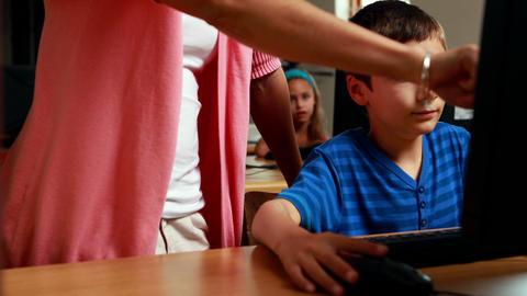 Teacher helping little boy in computer class Footage