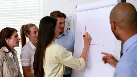 Casual business team watching colleague draw graph Footage