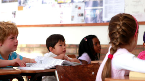 Cute pupils listening attentively in classroom Footage