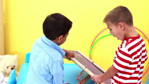 Cute little boys wiping and knocking over mini chalkboard Footage