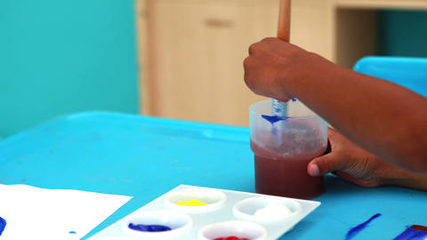 Cute little boys painting at table in classroom Footage