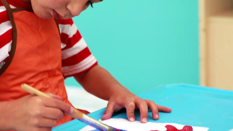 Cute little boy painting at table in classroom Footage