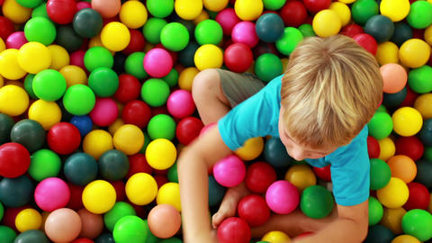 Cute boy playing and having fun in the ball pool Live Action