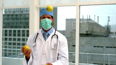 Doctor in mask juggling green apples Footage